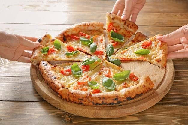 Jovens pegando fatias da deliciosa pizza margherita na mesa