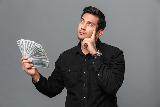 Jovens pensando concentrado homem segurando o dinheiro.