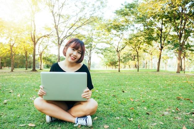 Jovens pernas da mulher asiática na grama verde com laptop aberto