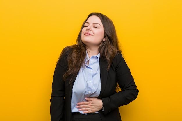Jovens plus tamanho mulher de negócios caucasiano toca a barriga, sorri suavemente, comendo e conceito de satisfação.