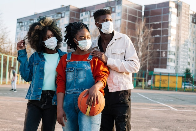 Jovens posando com máscaras médicas ao ar livre