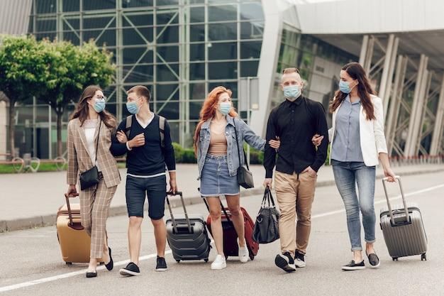Jovens positivos com máscaras protetoras com bagagem ao ar livre perto do aeroporto