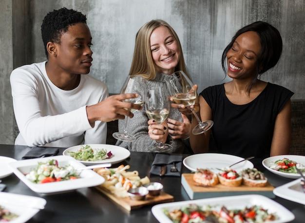 Jovens positivos jantando juntos