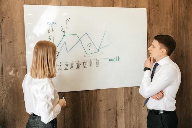 Jovens profissionais de negócios dois jovens colegas em roupas de escritório estão olhando para um quadro com uma programação enquanto passam algum tempo no escritório. foto de alta qualidade