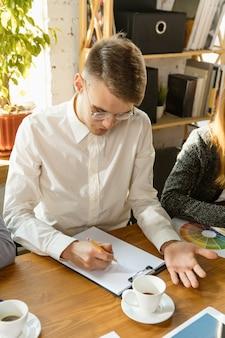 Jovens profissionais de negócios em reunião. grupo diverso de colegas de trabalho discutem novas decisões
