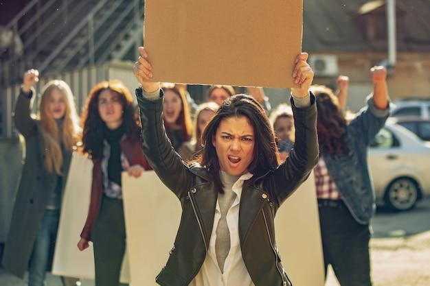 Jovens protestando pelos direitos das mulheres e igualdade nas ruas. mulheres brancas têm reuniões sobre problemas no local de trabalho, pressão masculina, violência doméstica, assédio. copyspace. segurando pôsteres.