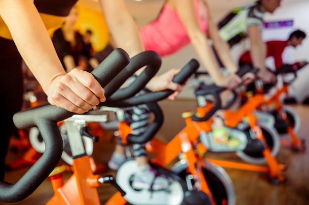 Jovens que elaboram em uma bicicleta de exercício no gym.