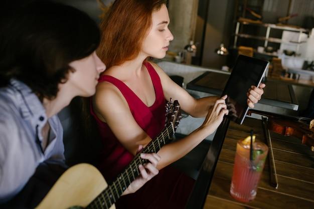 Jovens que procuram informações úteis online sobre como tocar violão. conceito moderno de benefícios de educação em tecnologia