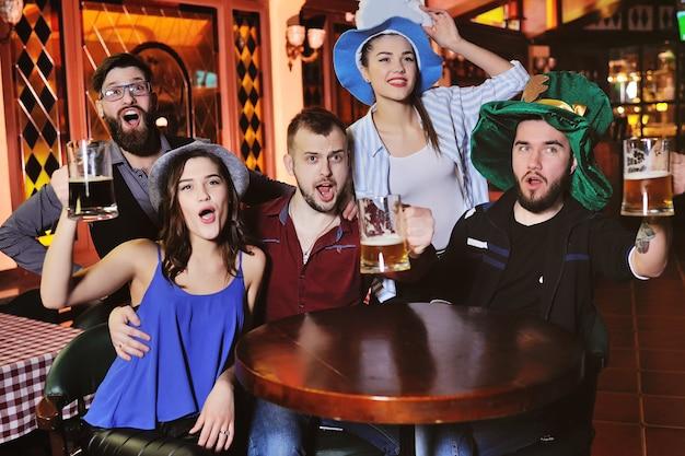Jovens rapazes e raparigas segurando copos de cerveja, assistindo futebol, rindo e sorrindo