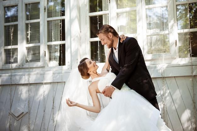 Jovens recém-casados elegantes bonitos sorrindo, dançando ao ar livre.