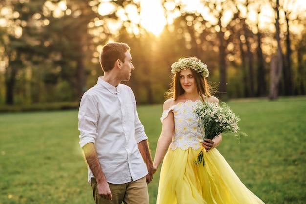 Jovens recém-casados felizes caminhando no parque ao pôr do sol