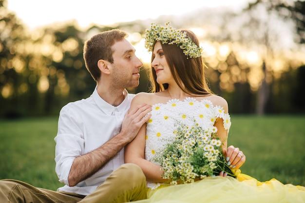 Jovens recém-casados felizes sentados na grama no parque ao pôr do sol