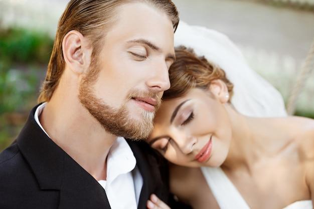 Jovens recém-casados lindos sorrindo com os olhos fechados, desfrutando.