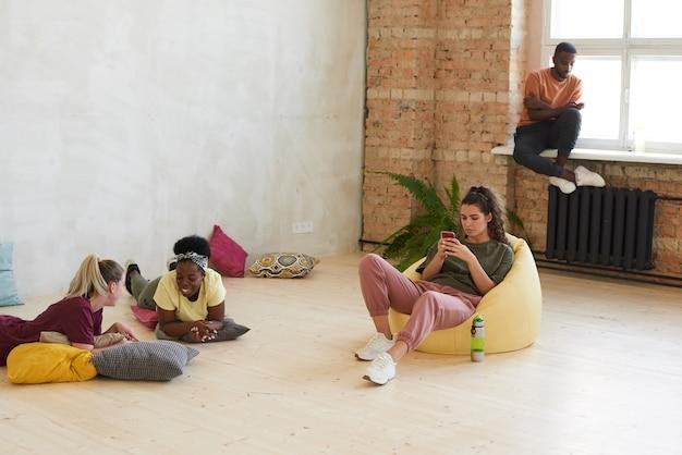 Jovens relaxando conversando e usando seus gadgets durante o intervalo do treinamento esportivo na academia