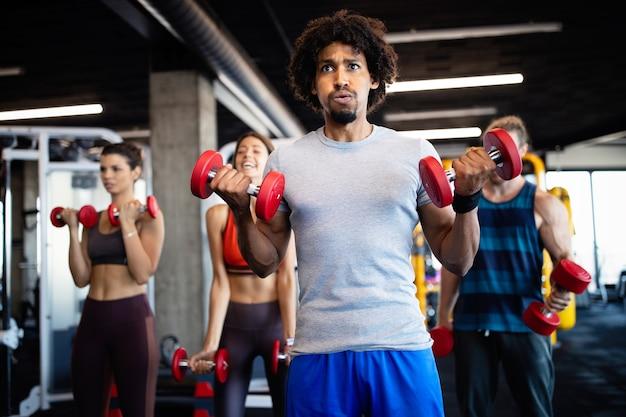 Jovens saudáveis cabem pessoas fazendo exercícios no estúdio de fitness.