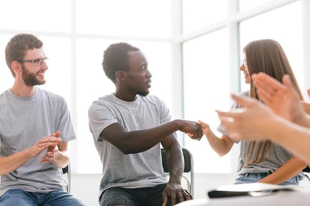 Jovens se cumprimentando com um aperto de mão
