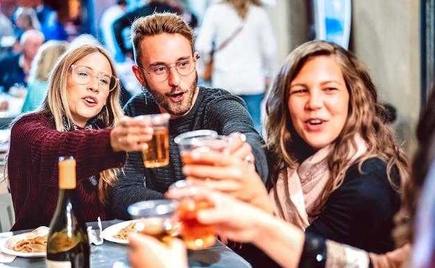 Jovens se divertindo brindando vinho branco no festival de comida de rua