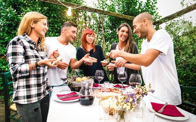Jovens se divertindo comendo comida local e bebendo vinho tinto no festival do jardim do campo - amizade e conceito de estilo de vida com amigos felizes juntos na festa no pátio da fazenda - filtro vívido quente