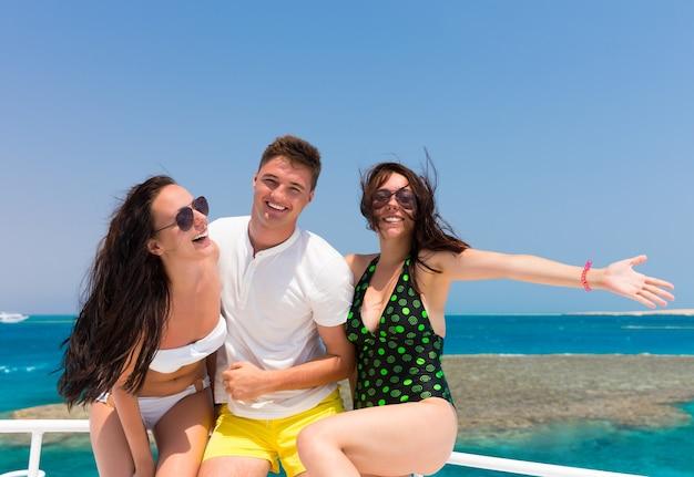 Jovens se divertindo e em pé no iate em um dia ensolarado de verão, brisa desenvolvendo cabelo, lindo mar ao fundo