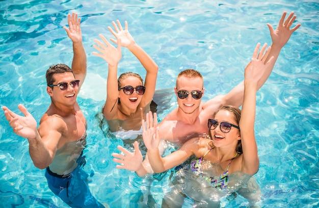 Jovens se divertindo na piscina, sorrindo.