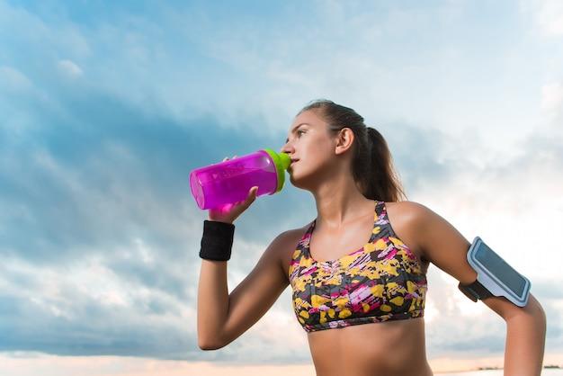 Jovens se encaixam garota bebendo água na praia após treino de manhã