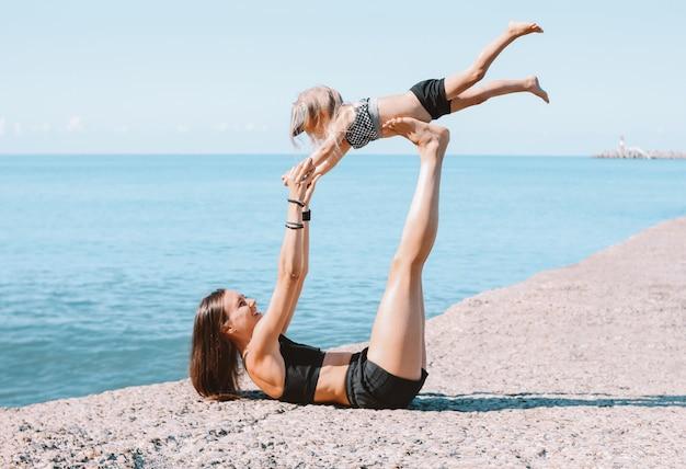Jovens se encaixam mãe mãe com menina bonita exercitando juntos na praia