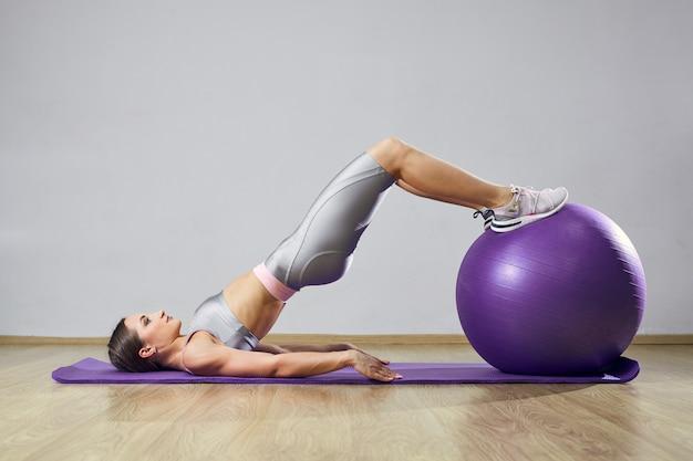 Jovens se encaixam mulher exercitando em uma academia. garota de esportes está treinando cross fitness com bolas de pilates.
