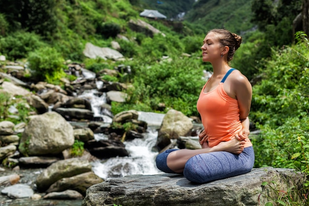 Jovens se encaixam mulher fazendo ioga oudoors na cachoeira