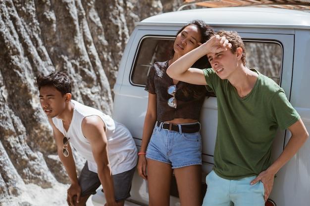 Jovens se sentindo cansado na parte de trás do carro avariado