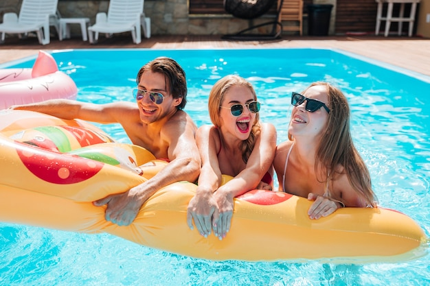 Jovens, segurando, um, pizza, natação, flutuador