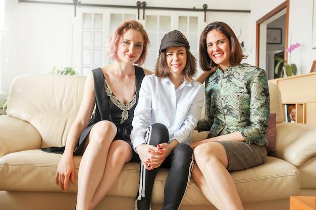 Jovens senhoras bonitas no sofá de couro