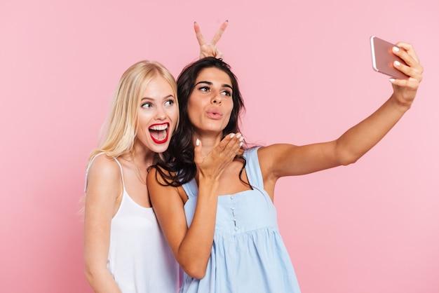 Jovens senhoras engraçadas fazendo selfie e sorrindo isolado