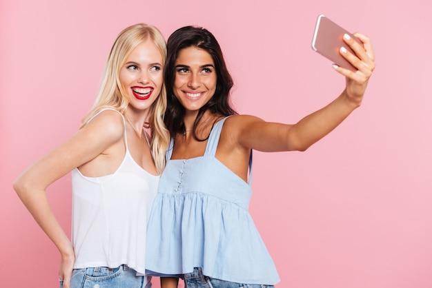 Jovens senhoras fazendo selfie e sorrindo isolado
