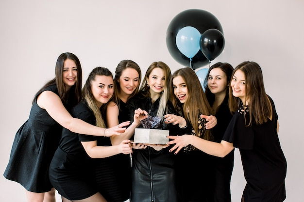 Jovens senhoras felizes em vestidos pretos, comemorando o aniversário no estúdio. melhores amigas de garota se divertindo segurando o bolo de aniversário e sorrindo. festa de aniversário, férias, conceito de dia das mulheres