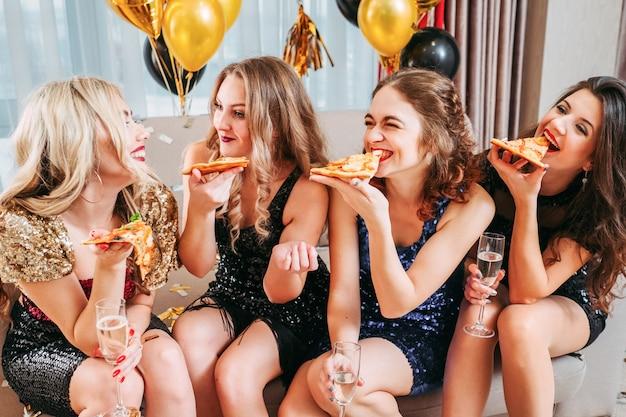 Jovens senhoras sentadas em uma sala decorada com balões, comendo pizza, conversando, sorrindo, se divertindo juntos.