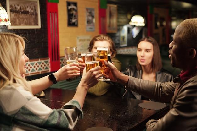 Jovens sentados à mesa bebendo cerveja durante reunião no bar