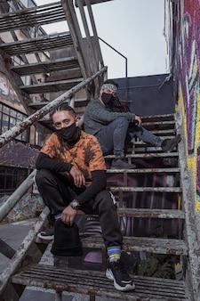 Jovens sentados em velhas escadas de metal