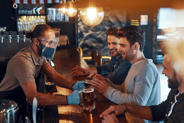 Jovens sorridentes em roupas casuais, bebendo cerveja e se unindo enquanto estão sentados em um bar
