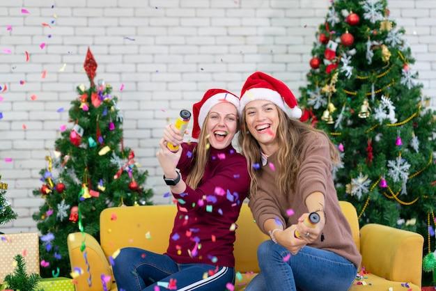 Jovens sorriem na temporada de inverno brincando e se divertem com os fogos de artifício de papel para comemorar na festa de natal