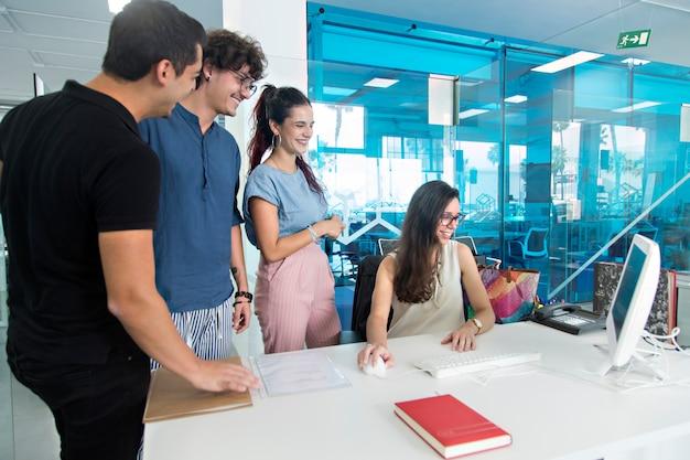 Jovens sorrindo e surpresos assistindo um computador em um escritório de coworking.