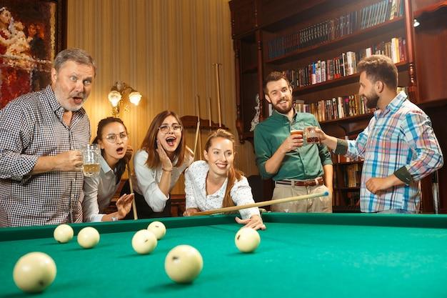 Jovens sorrindo, homens e mulheres jogando bilhar no escritório ou em casa, depois do trabalho. colegas de trabalho envolvidos em atividades recreativas. amizade, atividade de lazer, conceito de jogo.