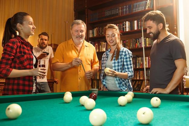 Jovens sorrindo, homens e mulheres jogando bilhar no escritório ou em casa, depois do trabalho. colegas de trabalho envolvidos em atividades recreativas