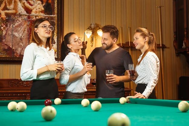 Jovens sorrindo, homens e mulheres jogando bilhar no escritório ou em casa, depois do trabalho.