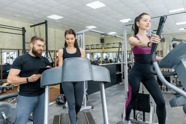 Jovens sorrindo mulheres fitness com personal trainer