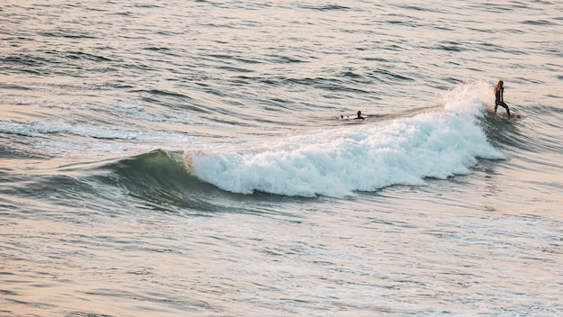 Jovens surfando no mar em um dia ensolarado