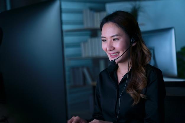 Jovens tailandeses asiáticos operadores de atendimento ao cliente trabalhando no turno da noite em call center