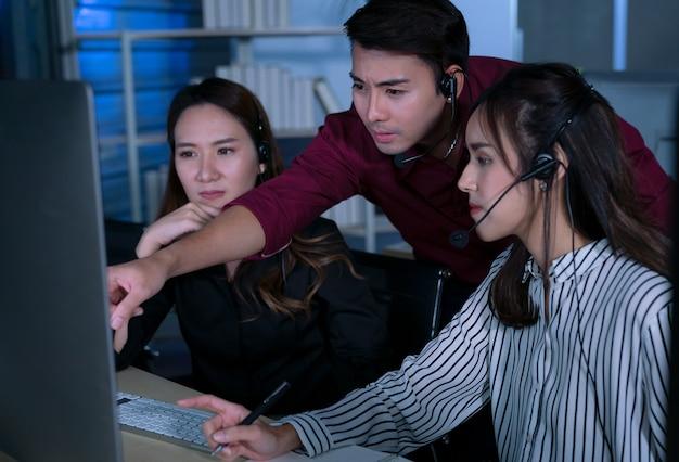 Jovens tailandeses asiáticos operadores de atendimento ao cliente trabalhando no turno da noite em uma central de atendimento para ajudar o cliente no local de trabalho à noite