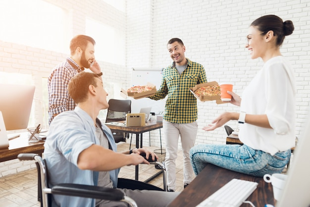 Jovens têm almoço com pizza no escritório.
