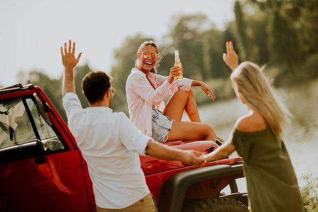 Jovens, tendo divertimento, em, carro conversível, por, rio