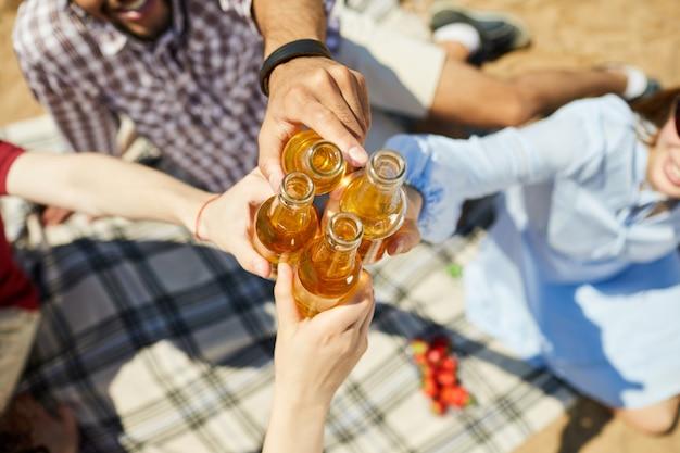 Jovens tinindo garrafas de cerveja